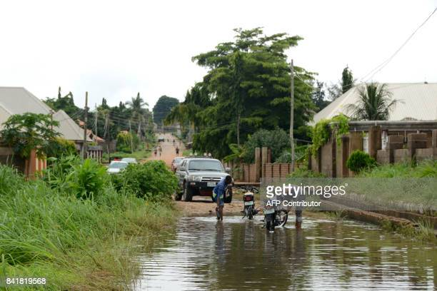 Men wash their motorbike as people evacuate the flooded area following heavy rains in Makurdi Benue State Nigeria on September 1 2017 At least one...