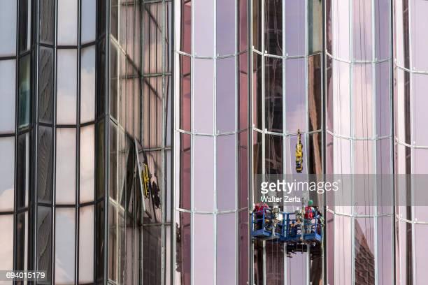 men washing windows on skyscraper - côte d'ivoire stock-fotos und bilder