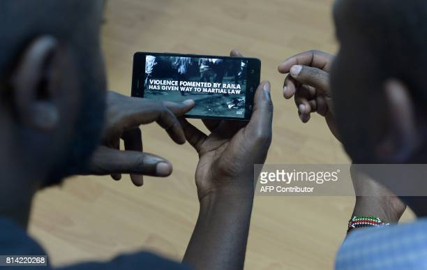 Men watch a campaign ad that was unleashed on the internet this week in Kenya just weeks before national elections on July 13 in Nairobi The 90...