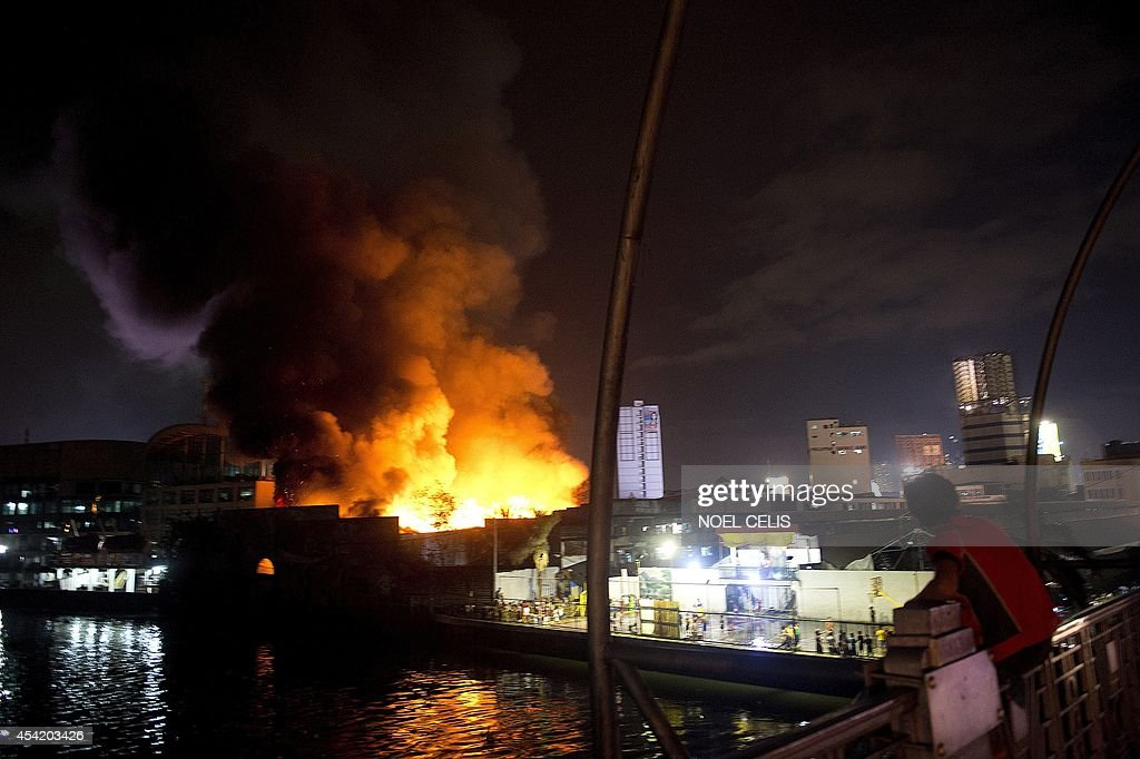 Men watch a fire that engulfed a warehouse in Manila on August 26, 2014.