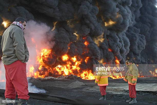 Men watch a giant fire early 14 February 2005 after insurgent attacks on oil and gas infrastructure near the northern Iraqi town of Kirkuk The gas...