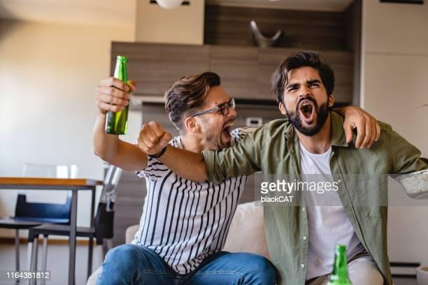 gli uomini guardano una partita sportiva - evento di calcio internazionale foto e immagini stock