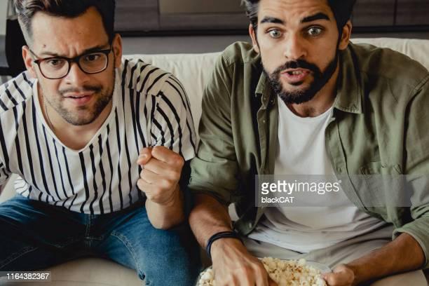 gli uomini guardano una partita sportiva - match sportivo foto e immagini stock