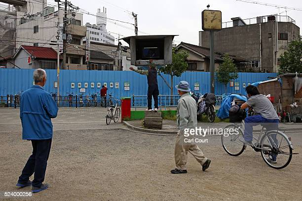 Men watch a television supplied by the local government in the slum area of Kamagasaki on April 24 2016 in Osaka Japan Kamagasaki a district in...