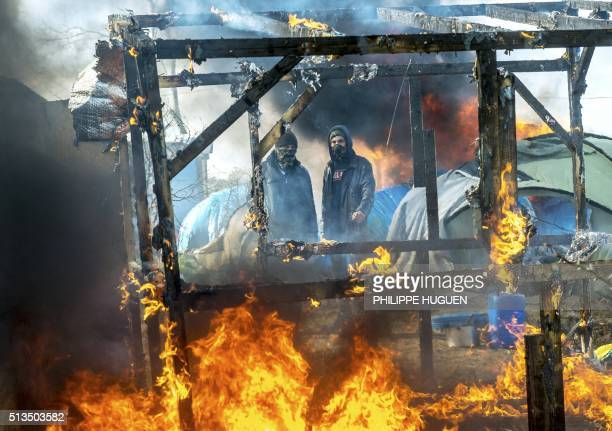 TOPSHOT Men watch as a makeshift shelter burns in the socalled Jungle migrant camp in the French port city of Calais on March 3 during the ongoing...