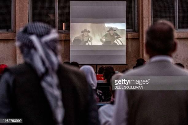 "Men watch as children attend a film screening as part of the mobile cinema ""Komina Film"" initiative organised by Syrian-Kurdish filmmaker Shero..."