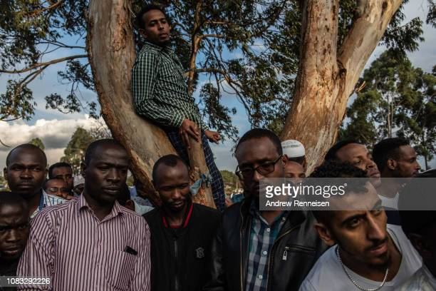 Men watch as the body of Abdalla Mohamed Dahir is buried on January 16 2018 in Nairobi Kenya Dahir and his colleague were killed after AlShabab...