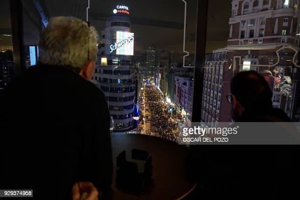 Men watch as thousands of people march down Gran Via street in Madrid on March 8 2018 during a one day strike to defend women's rights on...