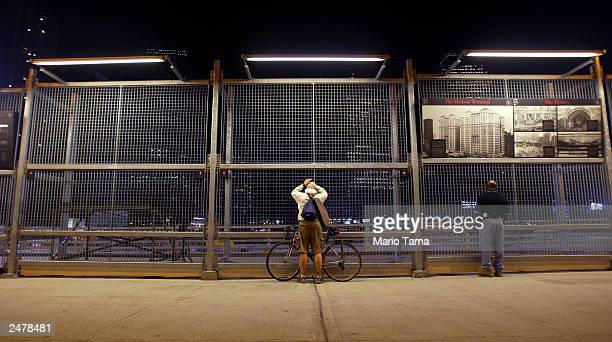 Men watch as work continues in the evening at Ground Zero September 9, 2003 in New York City. Thursday will mark the two-year anniversary of the...