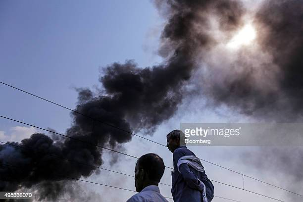 Men watch smoke billow from a fire in a rail yard at Mughalsarai Junction station in Mughalsarai Uttar Pradesh India on Thursday Oct 1 2015 The...