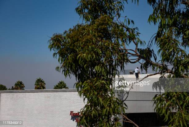 Men watch the fastmoving Saddleridge fire in the roof of a Sherman Oaks building in San Fernando Valley has charred dozens of homes closed freeways...