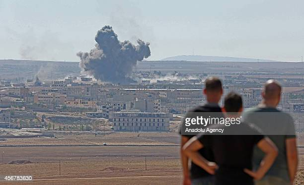 Men watch the smoke rising from Ayn alArab city of Syria after the USled coalition bombed the targets of the Islamic State of Iraq and the Levant in...
