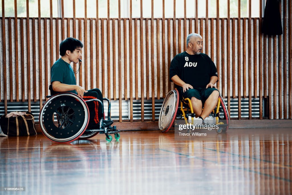 Men watching and officiating a wheelchair soccer game : ストックフォト