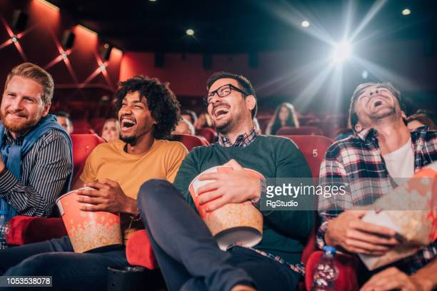 men watching comedy movie at cinema - comedy film stock photos and pictures