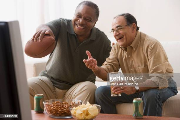 men watching football game in living room with snacks - old american football stock photos and pictures