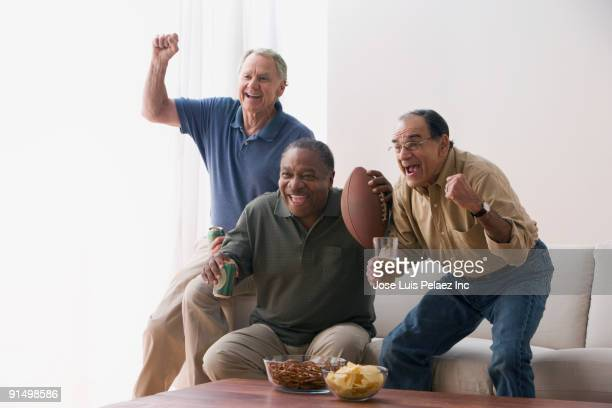Men watching football game in living room with snacks