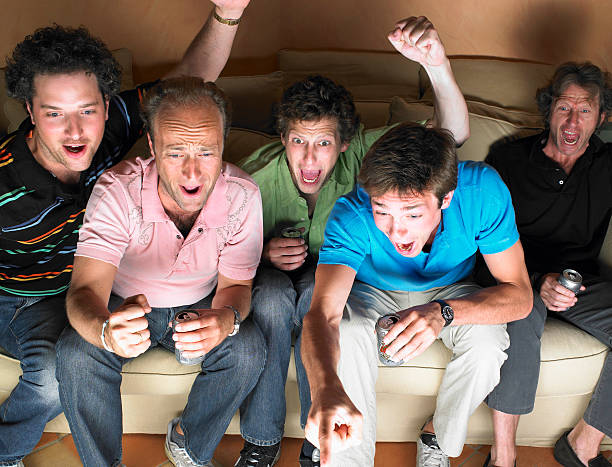 Men watching television, holding beers