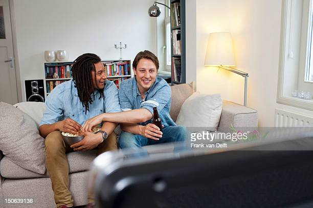 Men watching television in living room
