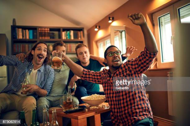 men watching television - man cave stock pictures, royalty-free photos & images