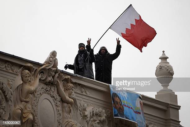Men wave a Bahraini national flag from the top of the Bahraini Embassy in central London on April 17, 2012 in London, England. The men continue to...