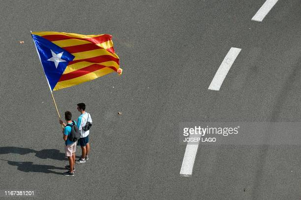 Men wave a Catalan proindependence Estelada flag during a demonstration marking the Diada national day of Catalonia in Barcelona on September 11 2019
