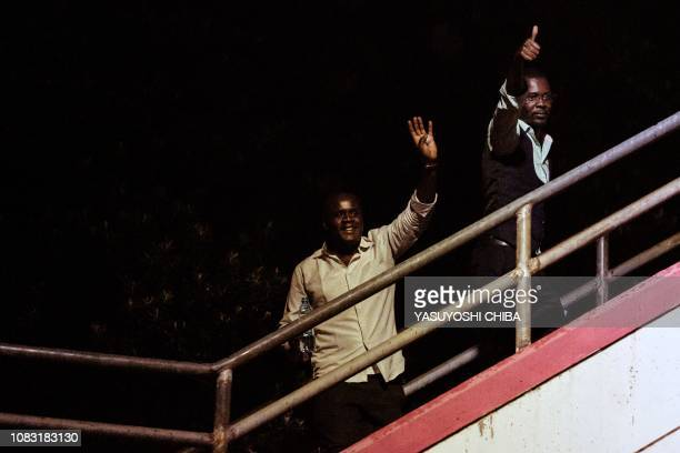 Men wave after being evacuated from the DusitD2 compound in Nairobi after a blast followed by a gun battle rocked the upmarket hotel complex on...