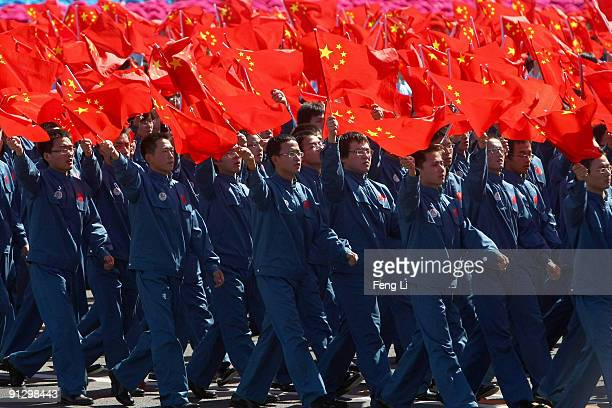 Men waves China's national flag as they take part in a parade to celebrate the 60th anniversary of the founding of the People's Republic of China on...