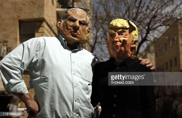 TOPSHOT Men wear masks depicting Israeli Prime Minister Benjamin Netanyahu and US President Donald Trump on the eve of the Jewish celebration of...