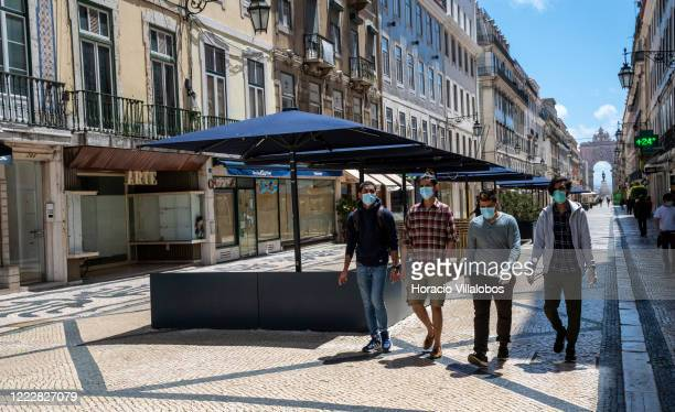 Men wear protective masks while walking in the almost empty Rua Augusta on the first day of the threestage reopening plan for activities disrupted by...