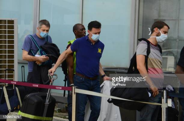 Men wearing a protective face mask wait in line during an evacuation of EU citizens members includes Germany France Austria Italy Spain Sweden Greece...