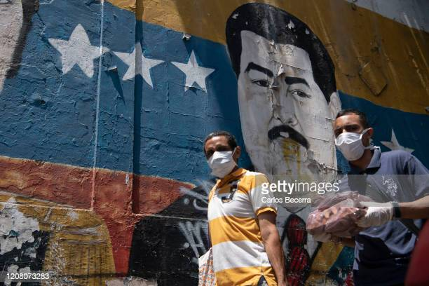 Men wearing a protective masks walk in Petare slum on March 23, 2020 in Caracas, Venezuela. While Nicol·s Maduro declared national quarantine, the...