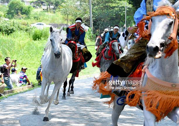 Men wearing ancient samurai warriors chase bareback horses to Soma Otaka Shrine during the 'Nomakake ' ritual as the conclusion event of the...