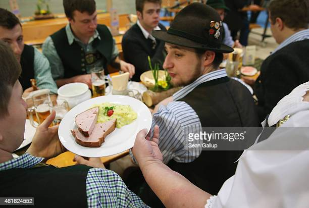 Men wearing Bavarian folk outfits lunch on beer liverwurst and potato salad at the International Green Week agricultural trade fair on January 16...