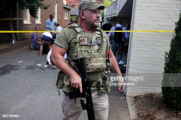Men wearing body armor combat weapons and patches that read New York Militia evacuate white nationalists neoNazis and members of the altright who...