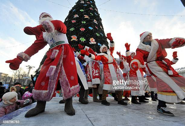 Men wearing costumes of Ded Moroz the Santa Claus in Russia Belarus and Ukraine dance during their parade in Minsk on December 25 2013 AFP PHOTO /...