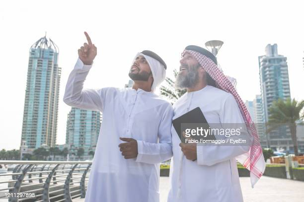 men wearing dish dash standing against buildings in city - united arab emirates stock pictures, royalty-free photos & images