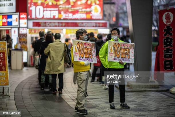 Men wearing face masks hold signs advertising the lottery on December 10, 2020 in Tokyo, Japan. Tokyo confirmed a record 602 new cases of Covid-19...