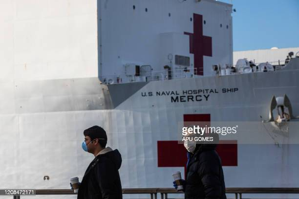 Men wearing facemaks as a preventive measure against the spread of the COVID19 novel coronavirus are seen walking with at the US Navy Hospital ship...