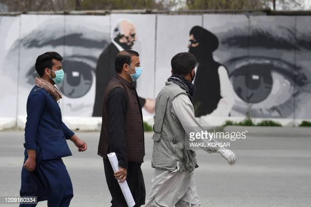 Men wearing facemasks as a precautionary measure against the COVID-19 novel coronavirus walk past a wall painted with images of US Special...