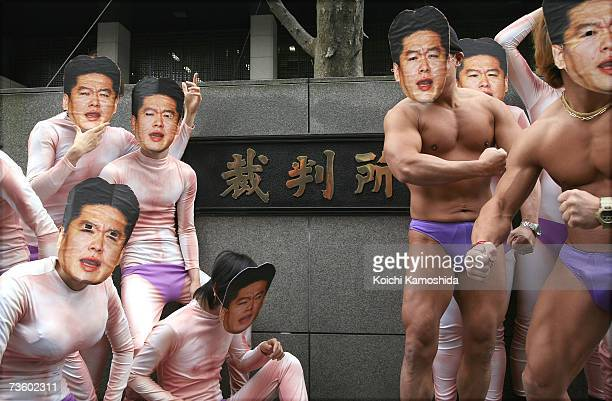 Men wearing masks of Takafumi Horie the founder and former President of Japanese Internet firm Livedoor Co pose in front of the Tokyo District Court...