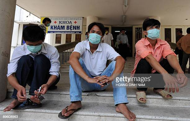 Men wearing masks sit on the doorsteps of the National Institute for Tropical diseases a main venue for swine flu patients in Hanoi on August 5 2009...