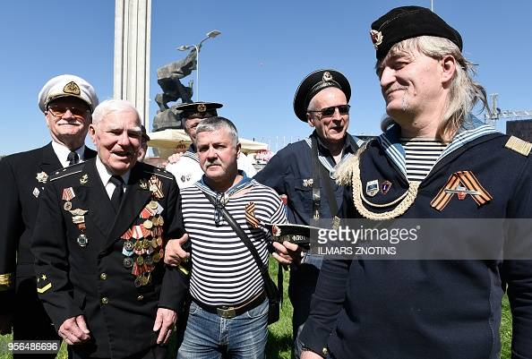 Men wearing medals and Guard ribbons gather at the Victory