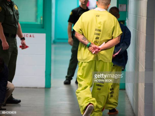 Men wearing neoncolored jail clothes signifying immigration detainees walk down a hall at the Theo Lacy Facility a county jail which houses convicted...