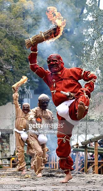 Men wearing ogre masks and costumes holding flaming torches dance during the Koshiki Tsuinashiki ritual at Nagata Shrine on February 3 2016 in Kobe...