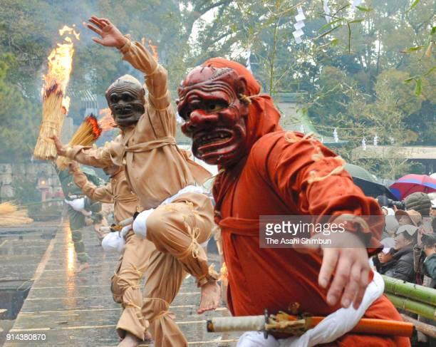 Men wearing ogre masks and costumes holding flaming torches dance during the Koshiki Tsuinashiki ritual at Nagata Jinja Shrine on February 3 2018 in...