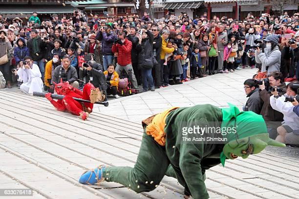 Men wearing ogre masks fall the slope as they are thrown beans during the Oniyarai ritual socalled beanscattering at Iwashimizu Hachimangu Shrine...