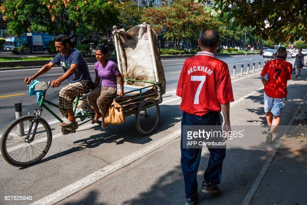 TOPSHOT Men wearing old Manchester United jerseys walk in the city of Skopje on August 8 2017 ahead of the UEFA Super Cup football match between Real...