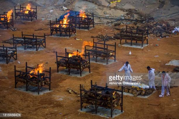 Men wearing PPE perform the last rites of a deceased relative in a disused granite quarry repurposed to cremate the dead due to COVID-19 on April 30,...