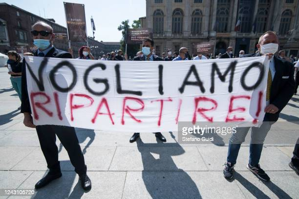 Men wearing protective face masks hold up a sign during a demonstration by bus drivers against the Italian Government for the economic problems the...