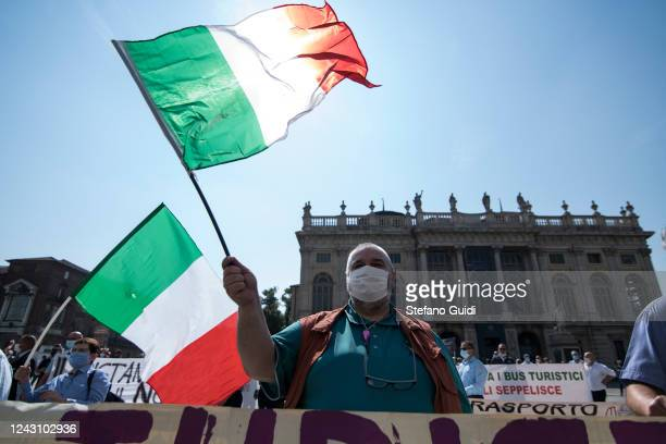 Men wearing protective face masks hold up Italian flags during a demonstration by bus drivers against the Italian Government for the economic...